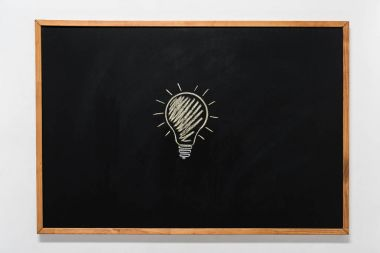 electric bulb drawn on black chalkboard