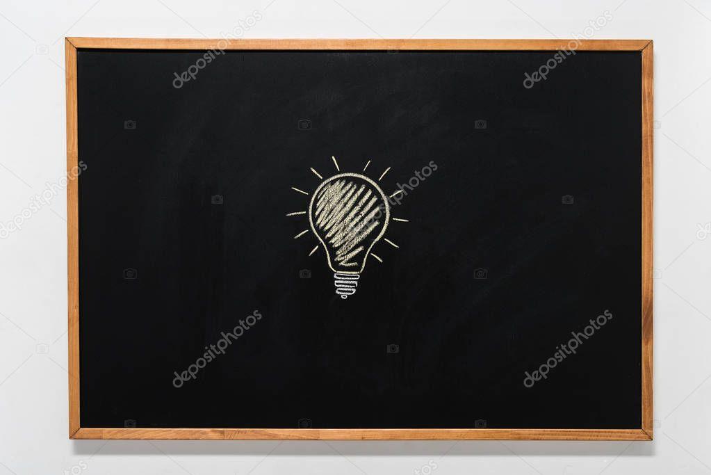 electric bulb drawn on black chalkboard