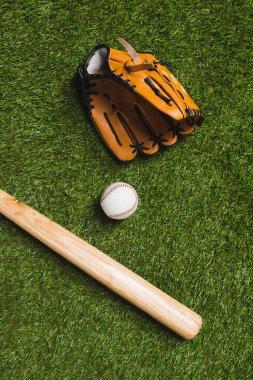 baseball bat with ball and glove on grass