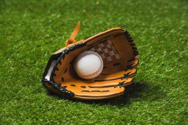 baseball glove with ball on grass