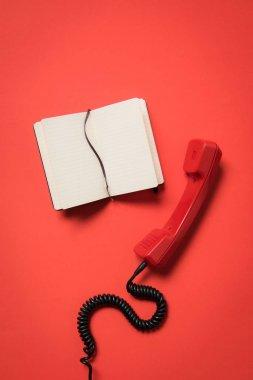 Telephone handset and blank notebook