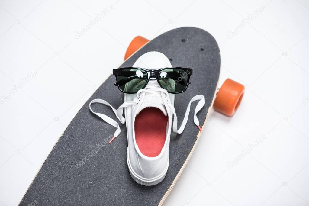 sneaker and sunglasses on skateboard