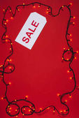 flat lay with price tag with sale lettering and christmas lights isolated on red