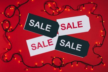 flat lay with price tags with sale lettering and christmas lights isolated on red