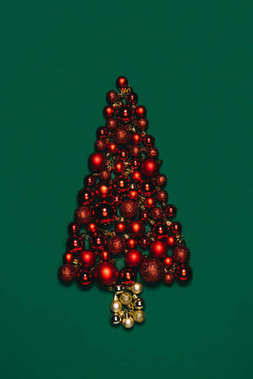 top view of christmas toys arranged into christmas tree isolated on green