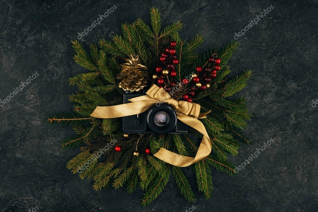 top view of photo camera and festive decorations on fir branches on dark tabletop