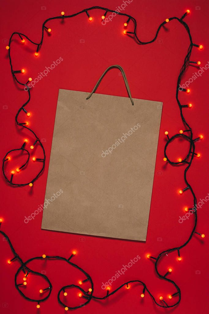 top view of empty paper bag and christmas lights isolated on red