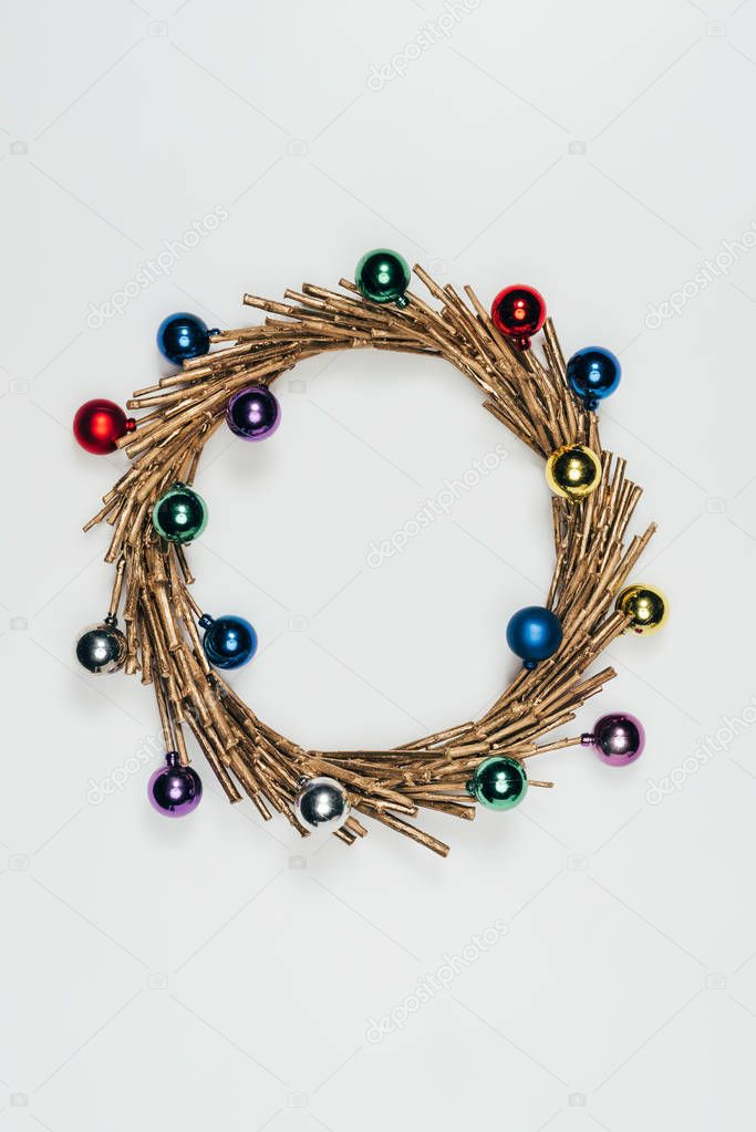 top view of christmas wreath with colorful decorative christmas balls isolated on white