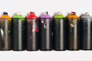 top view of arranged colorful spray paint in cans isolated on white