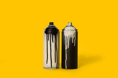close up view of black and white aerosol paint in cans isolated on yellow