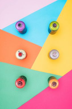 top view of arranged aerosol paint in cans on colorful background