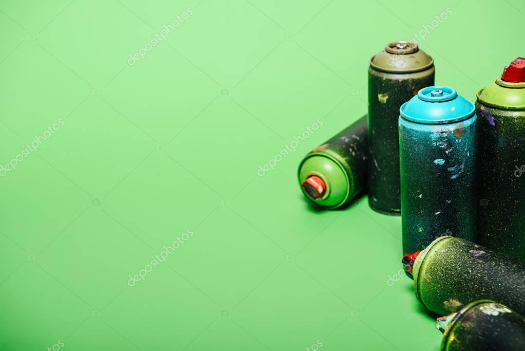 close up view of arranged cans with aerosol paint isolated on green