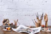 skici a poháry s kartáči na dřevěný stůl v dílně