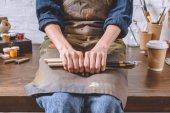 Fotografie oříznutý obrázek ženské umělce, sedí na stole a držení stopy