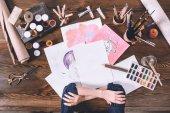Fotografia ritagliata colpo di mani femminili e schizzi con vernici al posto di lavoro di artista