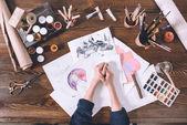 částečný pohled shora ženské ruce a náčrtky s barvami na pracovišti umělec