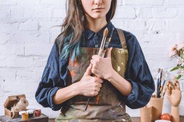 cropped image of female artist holding brushes