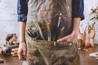 cropped image of artist with brushes and hand in apron pocket