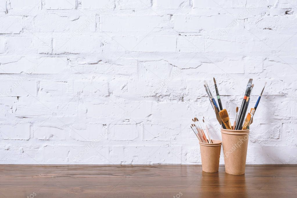 paint brushes in paper cups on white wall