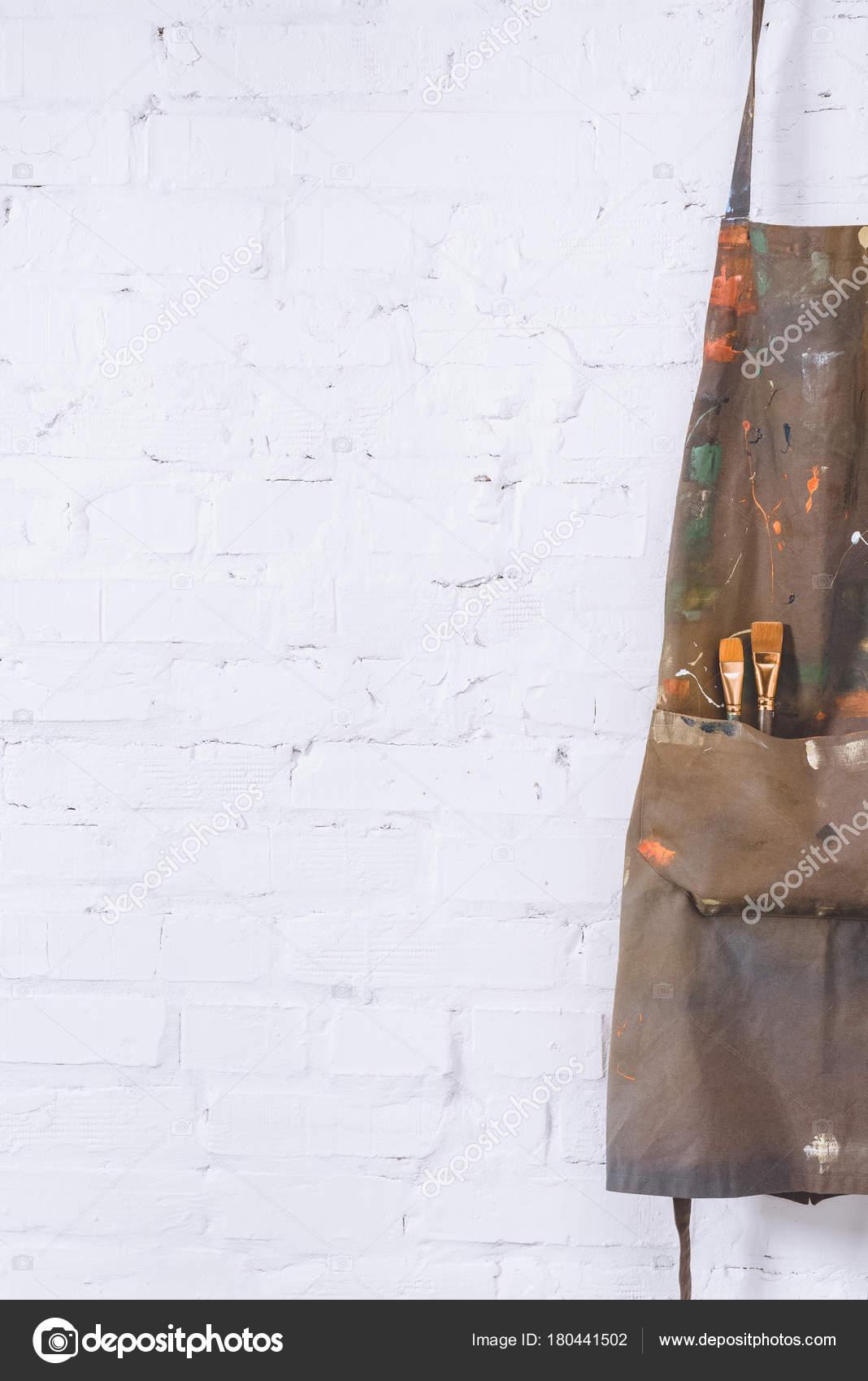 tablier marron avec brosses accroch sur mur briques. Black Bedroom Furniture Sets. Home Design Ideas