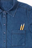 Photo close-up view of denim shirt with two pencils in pocket