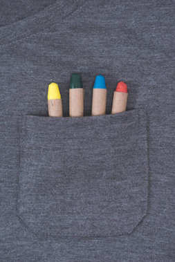 close-up view of grey male t-shirt with colorful crayons in pocket