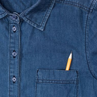 close-up view of stylish denim shirt with pencil in pocket