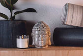 Photo sculpture of buddha head, burning candle and yoga mats on wooden shelf