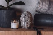Photo sculpture of buddha head and yoga mats on wooden shelf