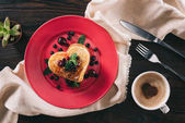 Fotografie top view of heart shaped pancake with berries and mint on wooden table, valentines day concept