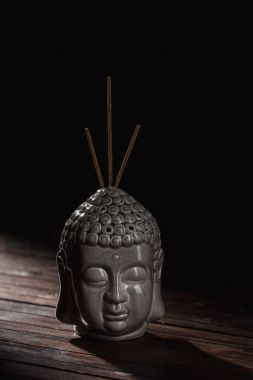 sculpture of buddha head with incense sticks