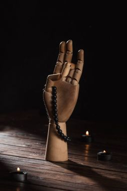 wooden hand with prithvi mudra gesture and rosary