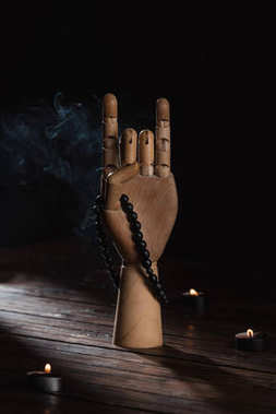 wooden hand with apan mudra gesture and rosary