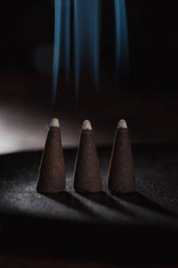 three burning incense sticks with smoke
