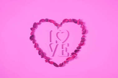 top view of heart from dried fruits with word love isolated on pink