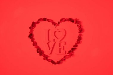 top view of heart from dried fruits with word love isolated on red