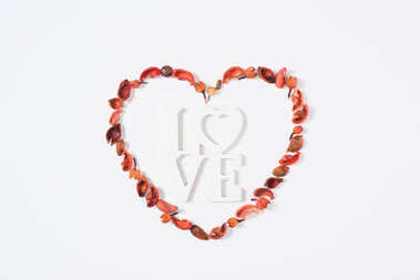 top view of heart from dried fruits with word love isolated on white
