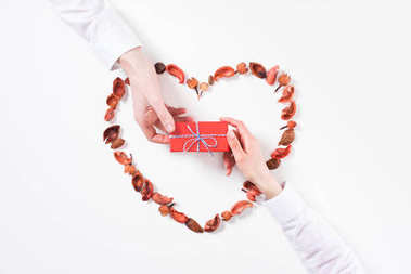 cropped image of boyfriend presenting girlfriend gift on valentines day isolated on white