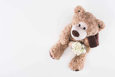 top view of teddy bear with bouquet of white flowers isolated on white