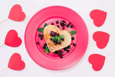 top view of heart shaped pancake and paper hearts isolated on white, valentines day concept