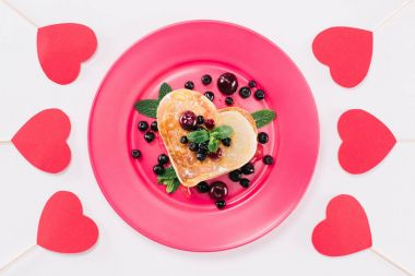 top view of heart shaped pancake with berries isolated on white, valentines day concept
