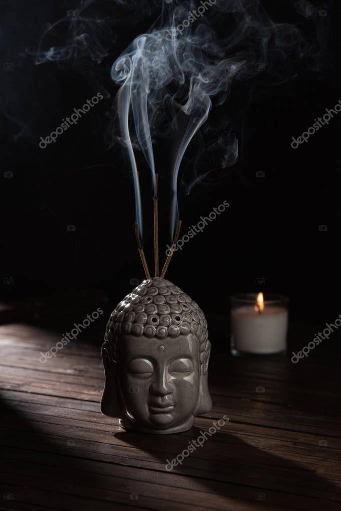 sculpture of buddha head with burning incense sticks and candle on table