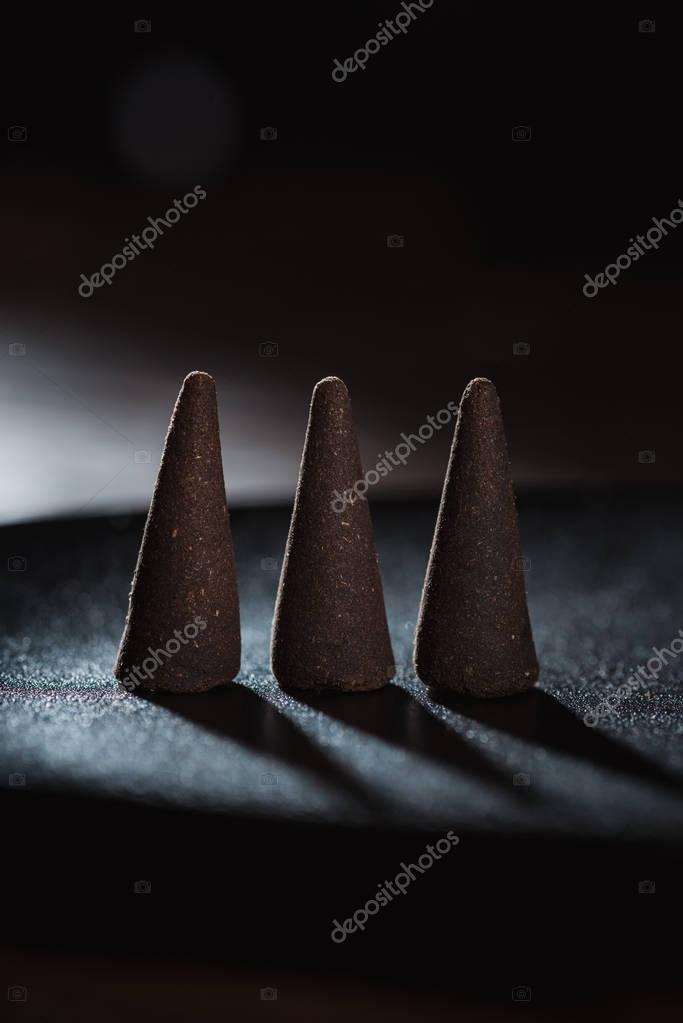 three incense sticks on dark surface
