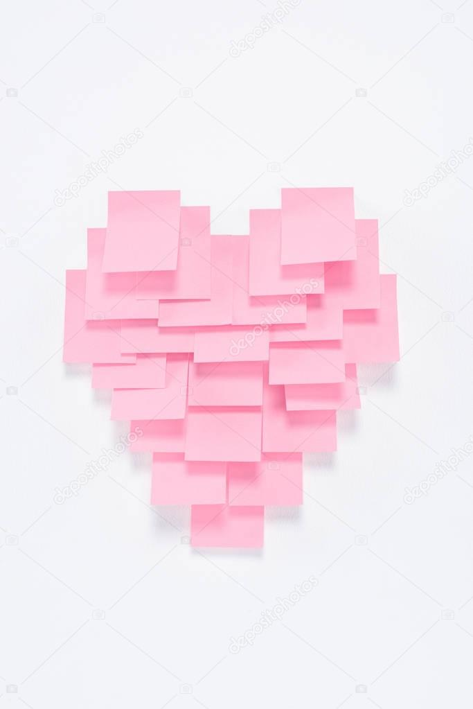 pink paper pieces in shape of heart on white, valentines day concept