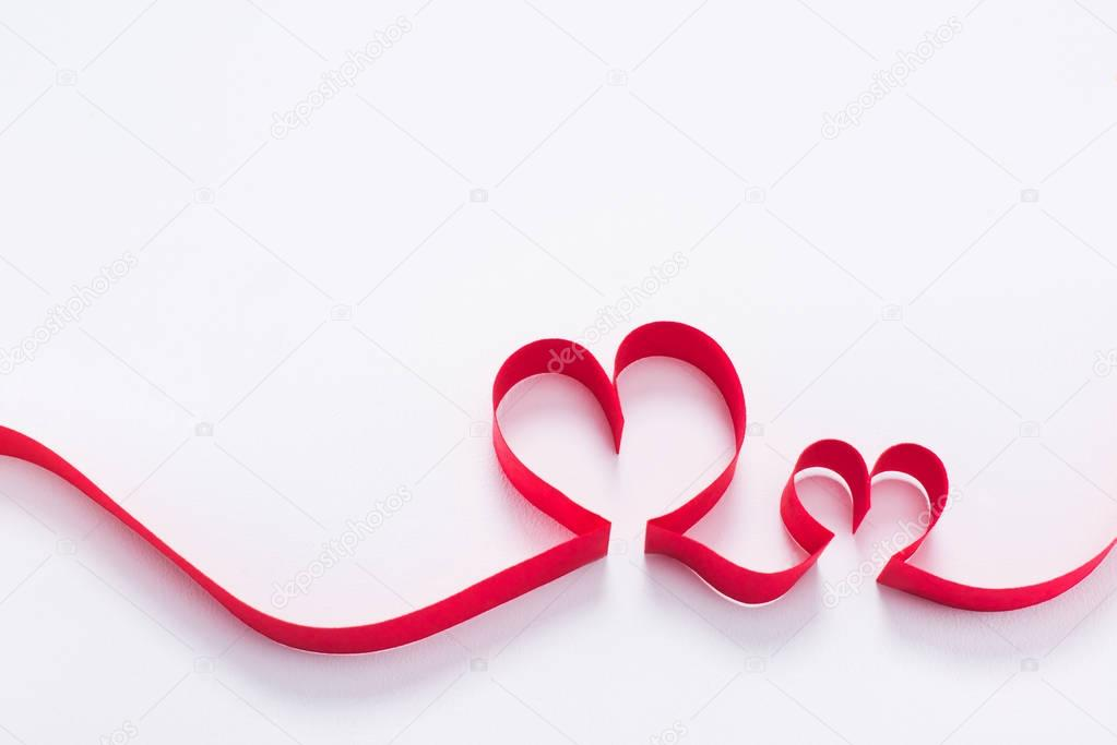 Two red hearts from ribbon on white, valentines day concept stock vector