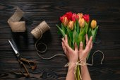 Fotografie partial view of female hands, rope, scissors and bouquet of flowers on wooden surface