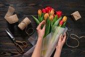 částečný pohled ženy obtékání Kytice tulipánů do balicí papír na dřevěnou desku