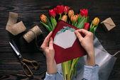 Schnappschuss einer Frau mit Postkarte in den Händen und Tulpen in Packpapier auf Holztischplatte