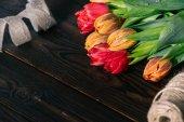 Fotografie zblízka pohled kytice tulipány, pásu karet a lana na dřevěnou desku