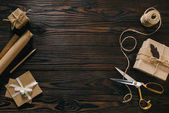 Photo flat lay with wrapped presents, rope and scissors on wooden surface